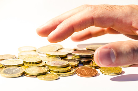grabbing: an hand is grabbing a group of different coins, (euro and cents), europe currency, over white Stock Photo
