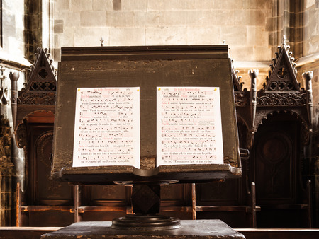 chant: details of a gregorian chant open on a woodemn music stand