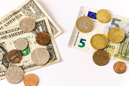 opposing: two group of bills and coins of euros and dollars, lay over white, face opposing