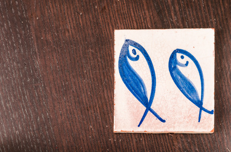 azulejos: tile with fishes drawing on it over a wooden table