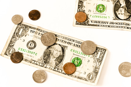 two us dollar: two usa dollars and coin lay scattered over white, business symbol for whealth and gain,
