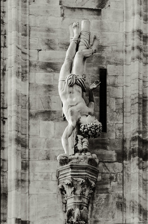 martyrdom: details of the lateral facade of milans cathedral. statue of a saint bond on a pole and upside down during his martyrdom Stock Photo
