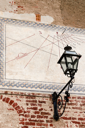 middle ages: view of a middle ages sundial painted over a wall, with an old-fashioned street light Stock Photo