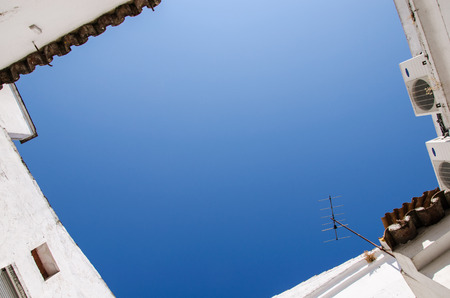 sensations: a corner of blue sky sorrounded by white house, copy space in the middle