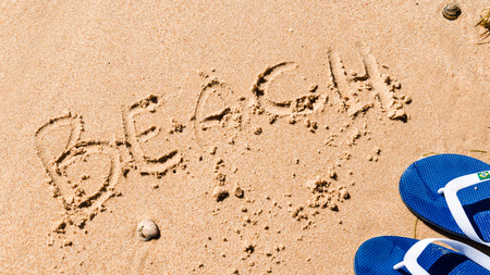wrote: the word beach wrote on the sand with a shell and blue flip-flops