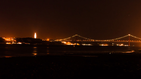 25th: cityscape of lisbon at night, view of the Tejo river with the 25th April bridge and the Christ redemptor.