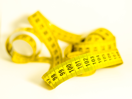 budget restrictions: still life with a yellow tape measure with the numbers hundred and hundredone in the foreground, symbol of success and goal