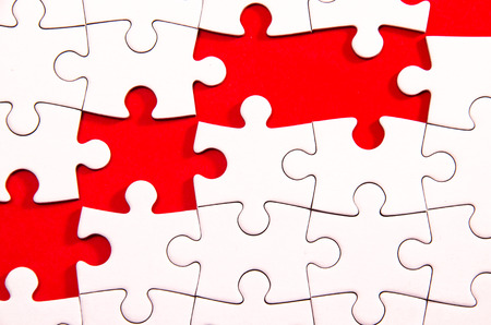 enigma: white jigsawpuzzle wite some gaps over red background, symbol of problem solving