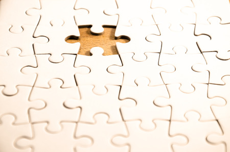 enigma: white jigsawpuzzle whit one gap, over a wooden table, symbol of problem solving Stock Photo