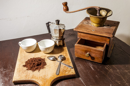 still life with a white two cups and two steel little spoons beside a pile of coffe powder  in the background a vintage coffee mill and an old coffee machine (moka)