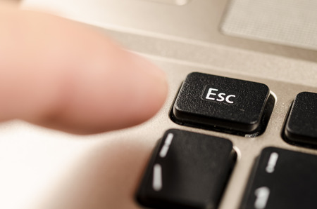 esc: close up of a  personal computer keyboard, with esc command and a finger that is going to press it