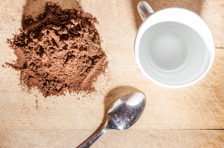 stell: stille life with a white cup and stell little spoon beside a pile of coffe powder