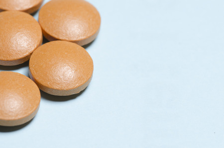 disease cure: group of orange pills over a pale blue background with copys space on the right. pharmaceutical. disease. cure. medicine