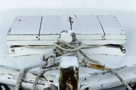 refelction: details of an old wooden boat anchored with a black rope Stock Photo