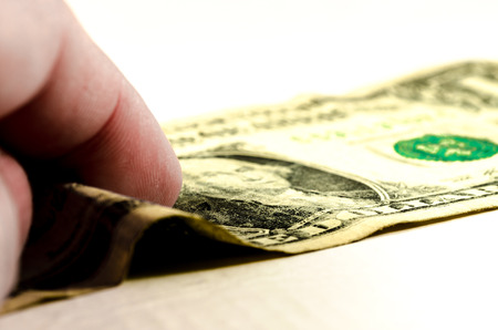 a human hand is taking a dollar bills over a white background. symbol of wealth Stock Photo