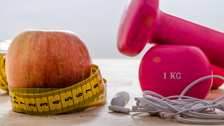 still life and close up with apple, pink weight, yellow tape measure. fitness and lifestyle concepts.