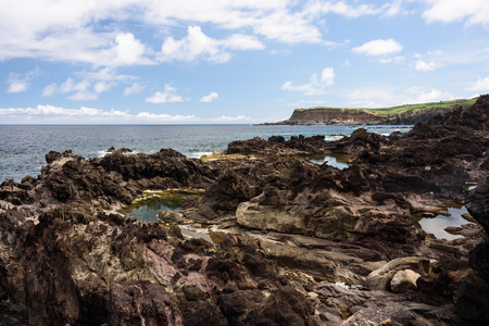 view of the rocky seaside in terceira with cliff in the background. seascape in azores, portugal.
