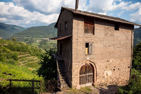 view of the facade of ah old rural house in dolomites (cembras valley) during summer, italy