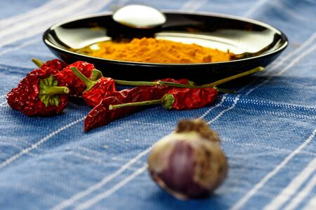 still life with red pepper over a blue tablecloth. with garlic and yellow powder. cooking spicy food.