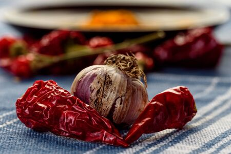 still life with garlic and chili pepper over a blue tablecloth. cooking spicy food. Imagens