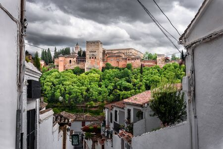 view of alhambra fro the narrow street in albaicin, the arab quarter in granada during a cloudy day. spain