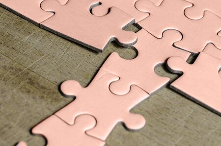 white jigsaw/puzzle with a row in wrong position, over  wooden table background, symbol of problem solving and new vision