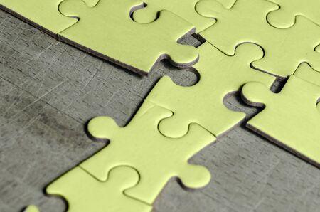 puzzle/puzzle blanc avec une rangée dans la mauvaise position, sur fond de table en bois, symbole de résolution de problèmes et nouvelle vision