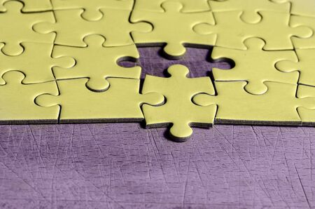 white jigsaw/puzzle with one piece at wrong position, over  black wooden table background, symbol of problem solving and new vision Banque d'images