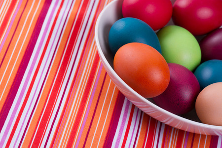 pascal: Colorful hand dyed easter eggs in a bowl on a table with striped tablecloth. Stock Photo