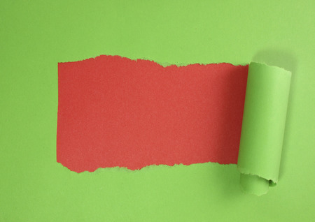 shredding: Torn green paper on red background