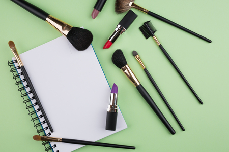 cosmetics products: decorative cosmetics with notebook on green background