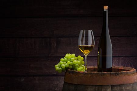 Botella de vino blanco y copa de vino en barril de madera Foto de archivo