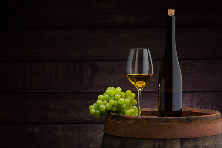 white wine bottle and wine glass on wodden barrel Foto de archivo
