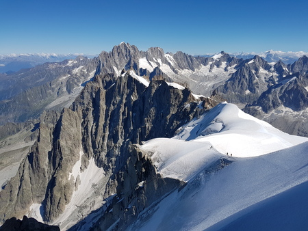 Panorama of the French Alps with climbers on the side of the mountain