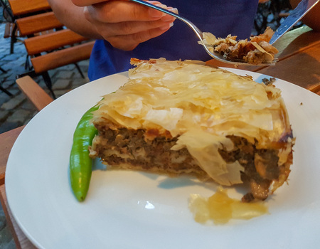 Fresh Romanian meat pie served in a white plate.