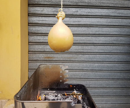 Typical Italian Cheese (Caciocavallo Impiccato) cooked on the grill with slices of bread.
