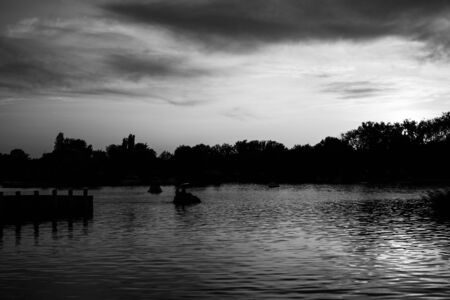 Calm black and white landscape with lake and lonely boats at sunset