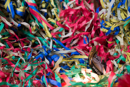 Close-up of Pierrot carnival mask on a background of colored streamers