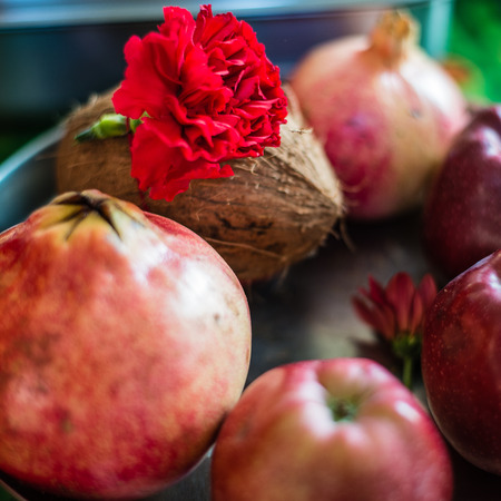 Group of fruits used as an offering with particular mantras prayers. Coconut pomegranates red apples and red flowers, are offered with particular mantras