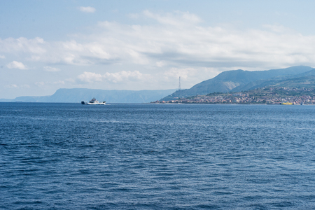 Overview of the Strait of Messina, with a ferry sailing in the open sea with the background of the city of Messina and the blue sky. Horizontal view
