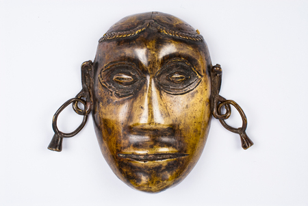 Close-up of a Naga tribal face in bronze from the Nagaland region, dating back to the 60s. Isolated on white background