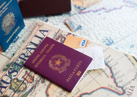 Milan, Italy – July 20, 2018 : An Italian and brasilian passports and a smartphone over a tourist magazine. Preparations for a trip in South America or Australia. Useful for travel agencies to advertise and promote travel for couples. Horizontal view