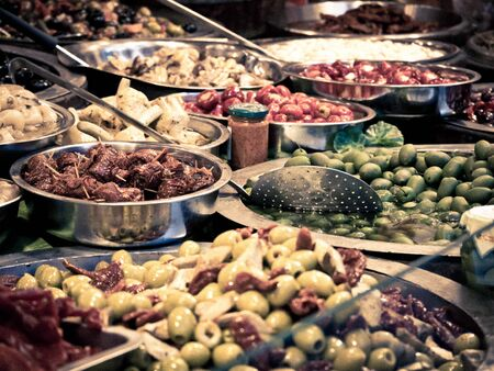 Close up of typical products of southern Italia Catania. Among these seasoned olives, artichokes in oil, seasoned dried tomatoes and other tasty Sicilian specialties. Horizontal view