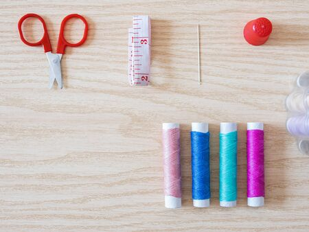 Spools of thread, bobbin, scissors and sewing accessories on a wooden background. Flatlay view.