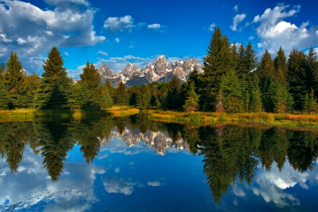 The range of tetons are reflected in the water photo