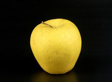 ailment: an organic yellow apple on black background