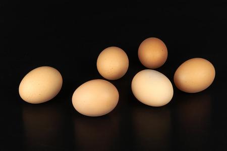 ailment: some eggs on black background Stock Photo