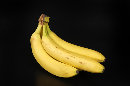 ailment: some  bananas on the black  background Stock Photo