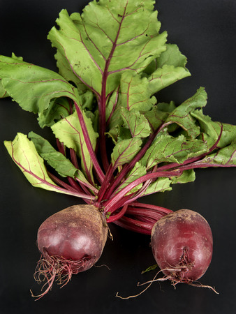 ailment: some red beetroots on black background