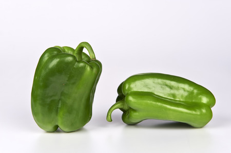 ailment: some biological green peppers on white background